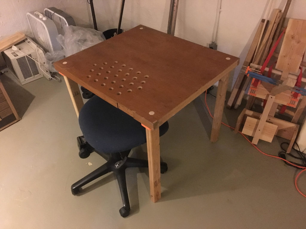A handmade scrapwood desk in a basement